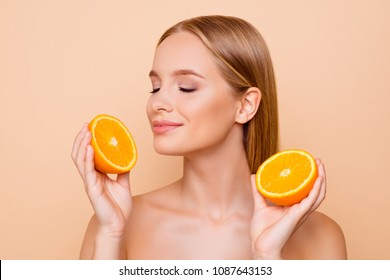 Portrait of joyful attractive pretty charming cheerful cute nude lovely dreamy natural girl having two pieces of orange, enjoying smell freshness with close eyes, isolated on beige background