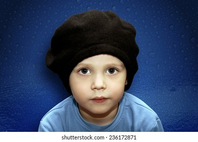 Portrait of joyful baby beret on the blue background.