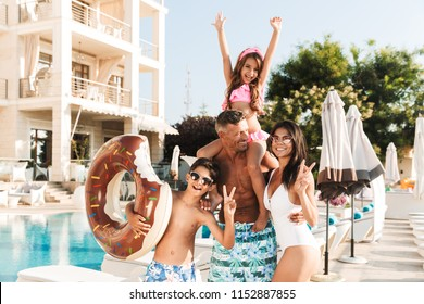Portrait of joyful beautiful family with children resting near luxury swimming pool and having fun with rubber ring outside hotel