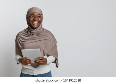 Portrait of joyful black muslim lady in hijab posing with digital tablet over light background in studio, happy african islamic woman in headscarf enjoying modern technologies and looking away