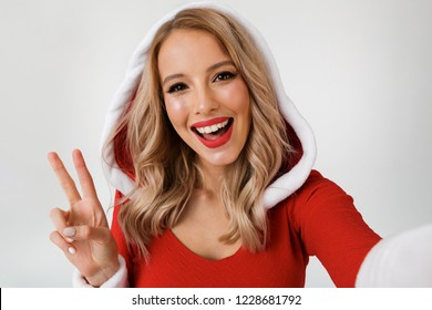 Portrait of a joyful blonde woman dressed in red New Year costume standing isolated over white background, taking a selfie
