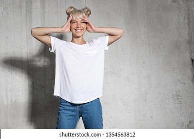 Portrait of joyful blonde woman touching head with hands. Female wearing stylish blue jeans and standing on concrete wall background. Copy space on shirt and right side