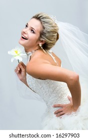 Portrait of joyful bride holding flower in hand and laughing while looking upwards