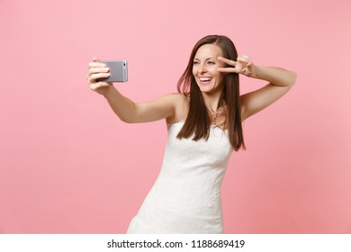Portrait of joyful bride woman in elegant white wedding dress showing victory sign doing taking selfie shot on mobile phone isolated on pastel pink background. Wedding celebration concept. Copy space