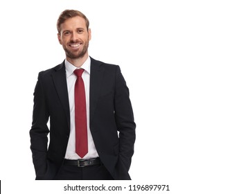 portrait of joyful businessman in suit and red tie standing on white background with hands in pockets
