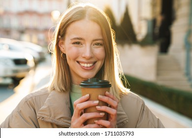 Portrait of joyful caucasian woman smiling and drinking coffee takeaway while walking at city street