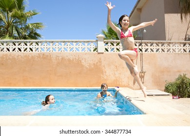 Portrait of joyful child boy having fun by swimming pool in home garden summer holiday, smiling with wet hair in swimwear outdoors playing with water pistol. Active kids lifestyle exterior vacation.