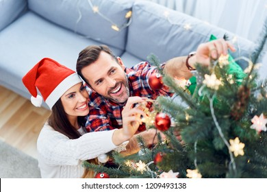 Portrait of joyful couple decorating christmas tree and spending time together during holiday