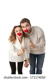 Portrait of joyful couple holding red hearts and laughing isolated on white