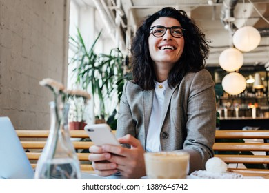 Portrait of joyful curly business woman sitting and working in city cafe with laptop, coffee and cake on the table. Holding mobile phone in hands and texting