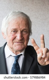 Portrait of joyful  elderly man of eighty years.Portrait of businessman looking at camera and raises two  fingers up and shows that all is well.