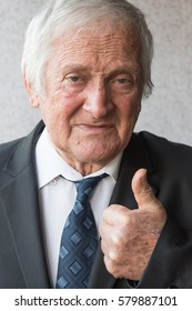 Portrait of joyful  elderly man of eighty years.Portrait of businessman looking at camera and raises  big thumb up and shows that all is well.