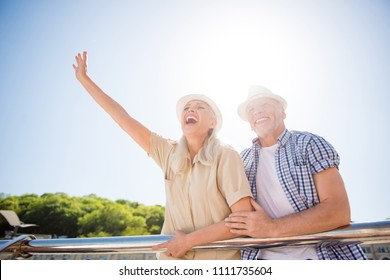 Portrait of joyful emotional couple in sunshine waiting for meeting with friends, shouting woman with raised hand gesturing hi symbol from balcony railing. Delight daydream concept