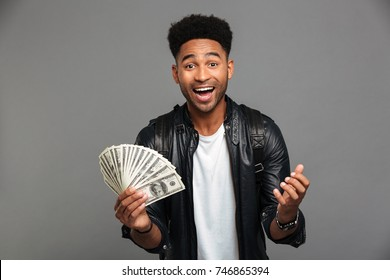 Portrait of a joyful excited afro american man in leather jacket holding money banknotes and looking at camera isolated over gray background