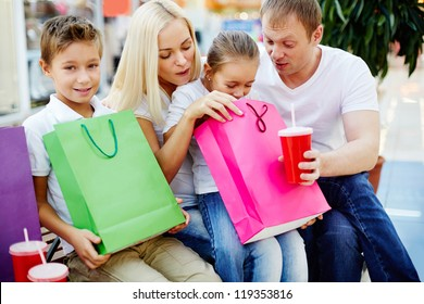 Portrait of joyful family having break and looking through paperbags in the mall
