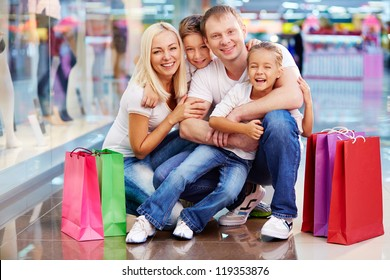 Portrait of joyful family with paperbags looking at camera in the mall