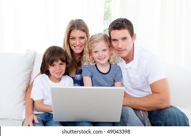 Portrait of a joyful family using a laptop sitting on sofa at home
