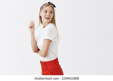 Portrait of joyful and fashionable european woman in red skirt and headband turning right while standing in profile with curious and interested expression seeing someone familiar and intriguing
