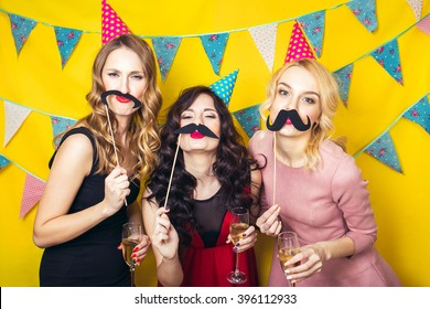 Portrait of joyful friends toasting and looking at camera at birthday party. Attractive friends celebrating a birthday. Smiling girls. Celebration and party. Having fun.