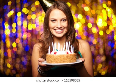 Portrait of joyful girl holding birthday cake and looking at camera at party