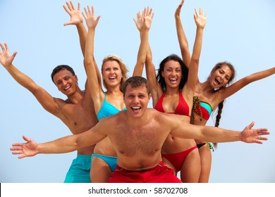 Portrait of joyful guy and happy girls in bikini on background looking at camera on summer vacation