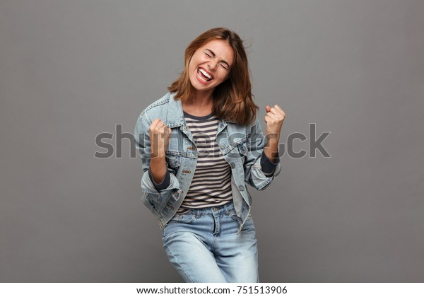 Portrait of a joyful happy teenage girl dressed in denim jacket celebrating success while dancing isolated over gray background