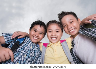 Portrait of joyful hugging kids looking at the camera, view from below