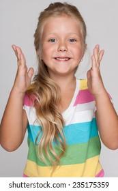 A portrait of a joyful little girl on the gray background