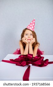 Portrait of joyful little girl in pink dress and hat put her elbows on big present gift box, at home birthday party streamers, Happy birthday. Celebrating, make faces