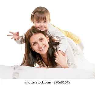Portrait of a joyful mother and her daughter in the bed on white background