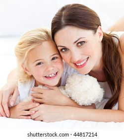 Portrait of a joyful mother and her daughter smiling at the camera