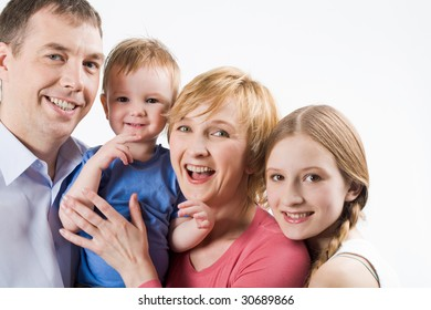 Portrait of joyful parents with their cute children looking at camera and smiling
