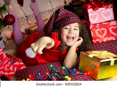 Portrait of joyful pretty girl in red santa claus hat laughing. Beautiful girl looking happy and excited. Happy Christmas and New Year holidays full of fun.