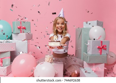 Portrait of a joyful pretty little girl in a birthday hat celebrating while sitting in a pile of present boxes and showing piece of cake isolated over pink background