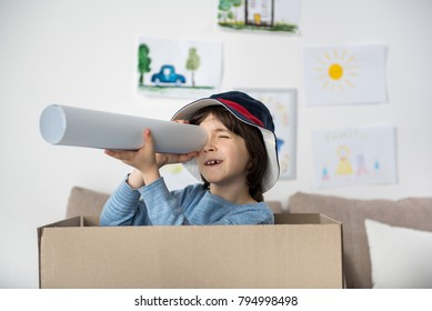 Portrait of joyful schoolboy standing inside of box and looking through rolled paper. Childish drawings hanging on wall