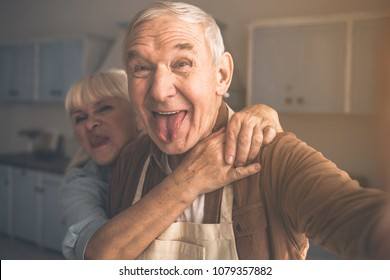 Portrait of joyful senior married couple having fun in cook room. They are taking photo of themselves and laughing while cuddling