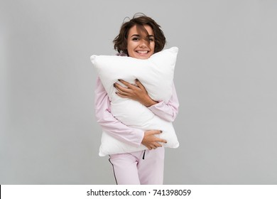 Portrait of a joyful smiling girl in pajamas holding a pillow and looking at camera isolated over gray background
