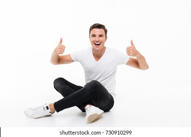 Portrait of a joyful smiling man in white t-shirt sitting on a floor and showing two thumbs up isolated over white background