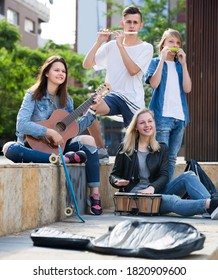Portrait of joyful smiling teenage band playing music together in the park .
