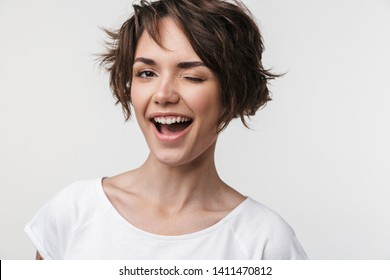 Portrait of joyful woman with short brown hair in basic t-shirt smiling at camera while standing isolated over white background