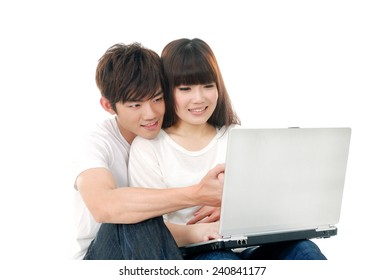 Portrait of a joyful young couple using laptop while sitting on the floor