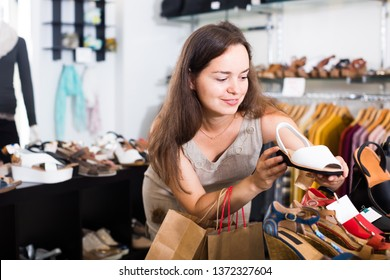 Portrait of joyful young female customer selecting shoes in footgear center