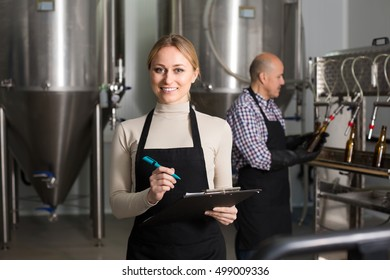 Portrait of joyful young female technologist on beer brewery factory