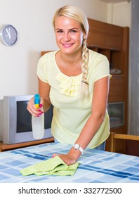 Portrait of joyful  young housewife dusting furniture at home