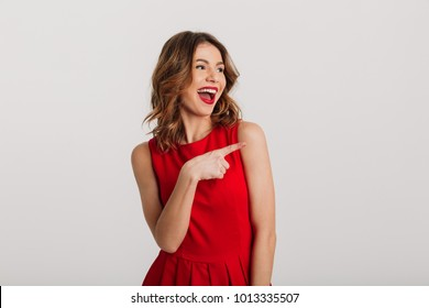 Portrait of a joyful young woman dressed in red dress pointing finger away at copy space isolated over white background