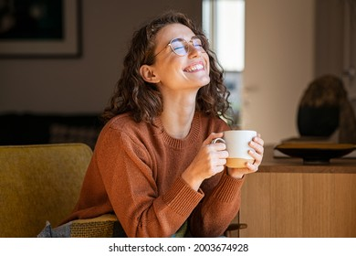 Portrait of joyful young woman enjoying a cup of coffee at home. Smiling pretty girl drinking hot tea in winter. Excited woman wearing spectacles and sweater and laughing in an autumn day.