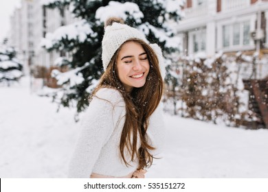 Portrait joyful young woman with long brunette hair having fun on street full with snow. Knitted hat, white woolen sweater, amazing smile, closed eyes, enjoying winter time