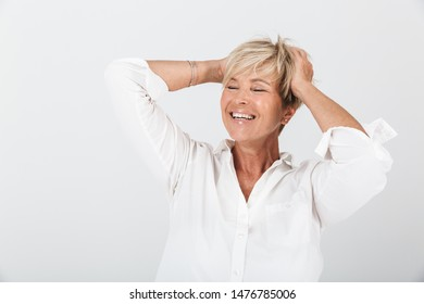 Portrait of joyous adult woman with short blond hair grabbing her head and laughing at camera isolated over white background in studio