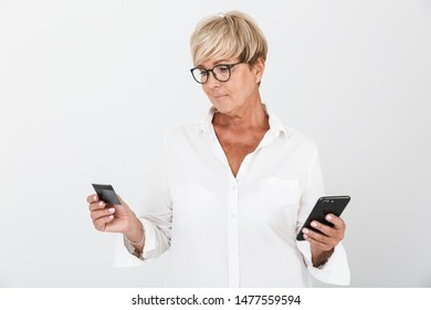 Portrait of joyous adult woman with short blond hair holding cellphone and credit card isolated over white background in studio
