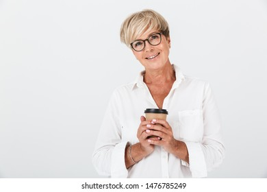 Portrait of joyous adult woman wearing eyeglasses holding takeaway coffee cup isolated over white background in studio